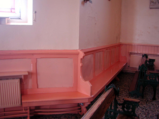 View of wainscoting with fixed pews.