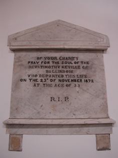 "View of cut-white marble Classical-style wall monument (ob. 1872) dedicated: ""OF YOUR CHARITY/PRAY FOR THE SOUL OF THE/REVd. TIMOTHY KEVILLE C.C./BALLINROBE/WHO DEPARTED THIS LIFE/ON THE 23RD OF NOVEMBER 1872/AT THE AGE OF 33/R.I.P.""."