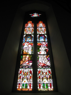 "View of Egan Memorial Windows signed (1888) by Franz Mayer and Company (founded 1847) of Munich and London depicting ""The Nativity"" and ""The Purification or The Presentation in The Temple"" dedicated: ""PRAY FOR THE SOUL OF WILLIAM EGAN/Mayer & Co. Munich & London [studio signature]""."