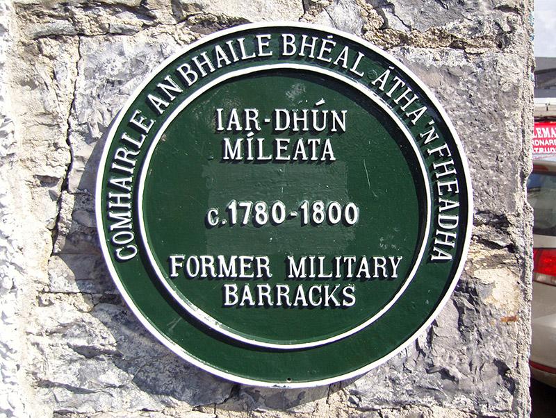 "View of castiron ""heritage plaque"" embossed: ""Comhairle An Bhaile Bhéal Atha 'nFheadha/Lar-Dhún/Míleata/c.1780-1800/Fomrer Military/Barracks""."