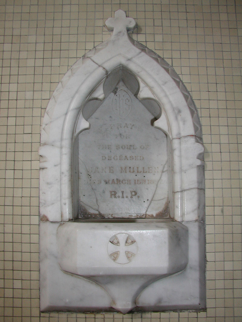 """View of cut-white marble Gothic-style memorial stoup (ob. 1897) dedicated: """"IHS/Pray/For/The Soul Of/Deceased/Jane Mullen/Died March 15th 1897/RIP""""."""