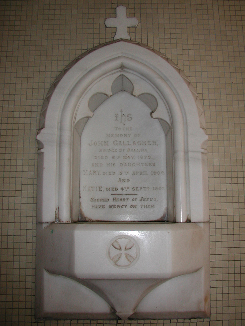 """View of cut-white marble Gothic-style memorial stoup (ob. 1879) dedicated: """"IHS/To The/Memory Of/John Gallagher/Bridge Street Ballina/Died 6th November 1879/And His Daughters/Mary Died 5th April 1904/And/Katie Died 4th September 1907/Sacred Hear Of Jesus/Have Mercy On Them""""."""