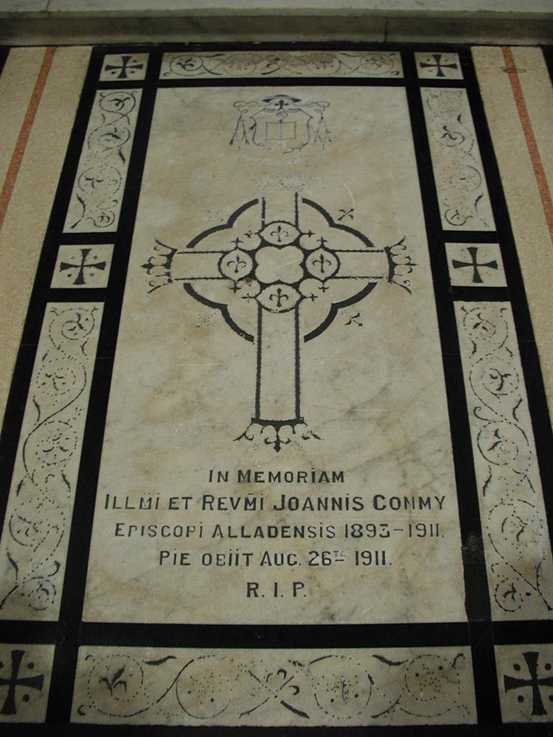 "View of inlaid cut-white marble floor monument (ob. 1911) dedicated: ""In Memoriam/Illmi Et Revmi Joannis Conmy/Episcopi Alladensis 1893-1911/Pie Obiit Augustus 26a 1911/RIP""."