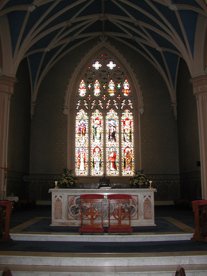 """View of interior including view of Feeny Memorial """"East Window"""" (ob. 1873) signed by Franz Mayer and Company (founded 1847) of Munich and London depicting (top) """"Saint Lawrence O'Toole""""; """"Saint Patrick""""; """"Saint Bridget"""" and """"Saint Kevin"""" and  (bottom) """"Saint Muredock""""; """"Saint Dympna""""; """"Saint Asicus"""" and """"Saint Columbkill"""" dedicated: """"In Memoriam Reverend Thomas Feeny Epi Alladensis 1839-73 RIP/Mayer And Company Munich And London [studio signature]""""."""