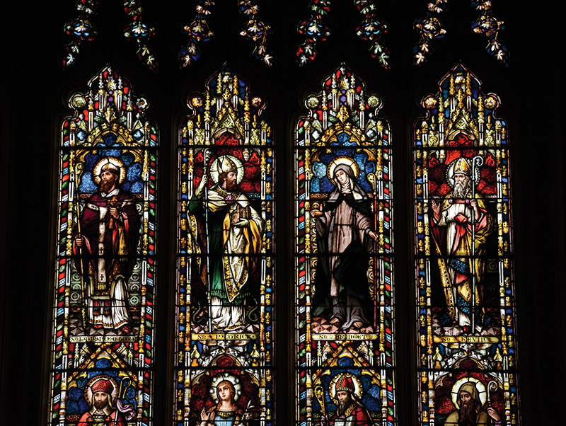 """Detail of Feeny Memorial """"East Window"""" (ob. 1873) signed by Franz Mayer and Company (founded 1847) of Munich and London depicting (top) """"Saint Lawrence O'Toole""""; """"Saint Patrick""""; """"Saint Bridget"""" and """"Saint Kevin"""" and  (bottom) """"Saint Muredock""""; """"Saint Dympna""""; """"Saint Asicus"""" and """"Saint Columbkill"""" dedicated: """"In Memoriam Reverend Thomas Feeny Epi Alladensis 1839-73 RIP/Mayer And Company Munich And London [studio signature]"""".  Photography by James Fraher"""