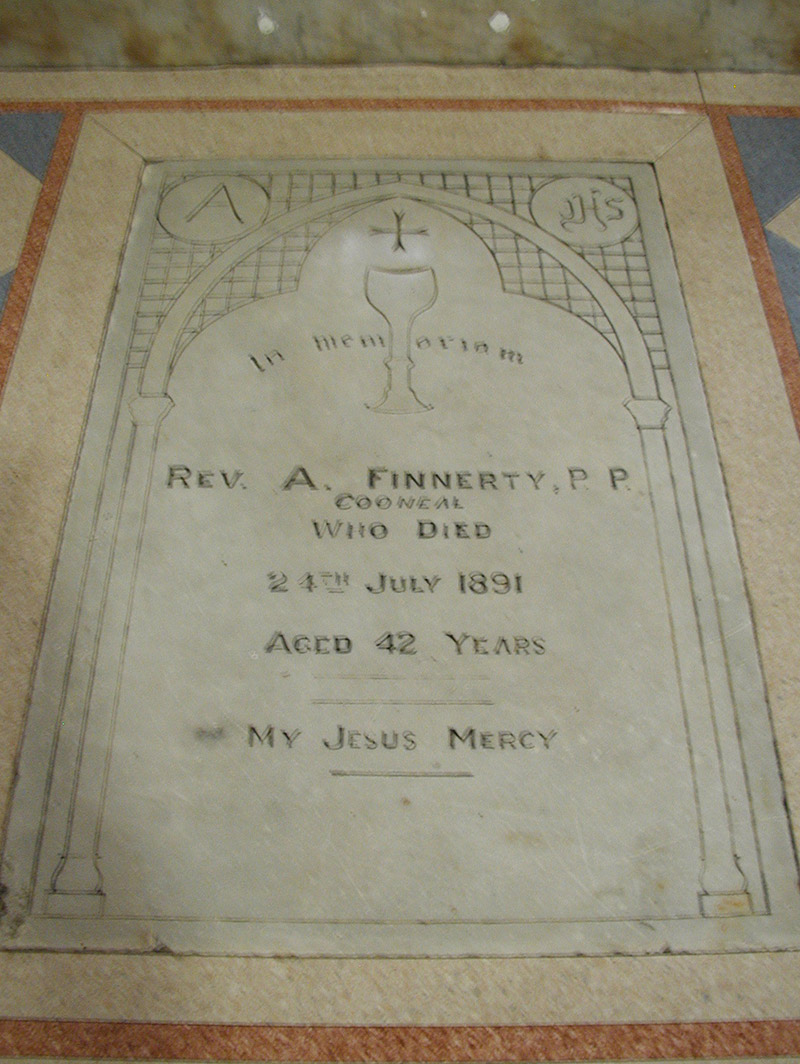 """View of inlaid cut-white marble floor monument (ob. 1891) dedicated: """"In Memoriam/Reverend A. Finnerty PP/Cooneal/Who Died/24th July 1891/Aged 42 Years/My Jesus Mercy""""."""