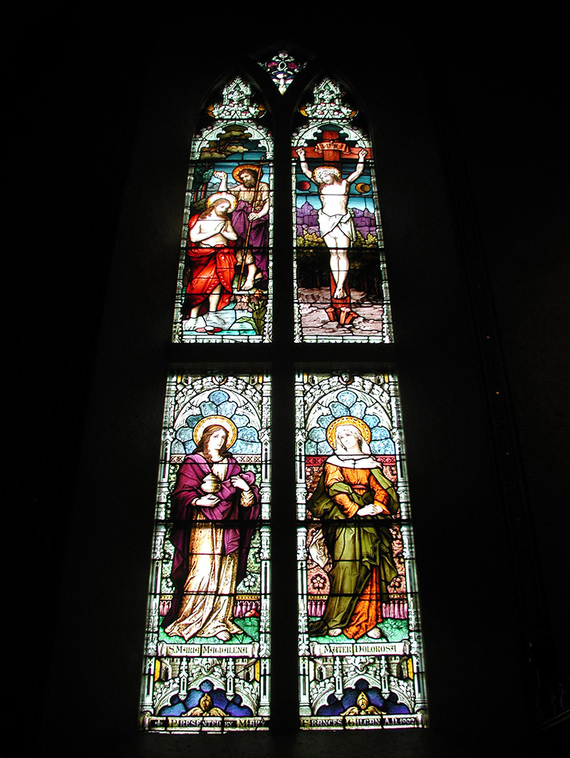 """View of Gilgan Memorial Window (1902) by ???? (????) of ???? depicting (top) """"The Baptism of Christ"""" and """"The Crucifixion"""" and (bottom) """"Saint Mary Magdalene"""" and """"Mater Dolorosa [Our Lady of Sorrows]"""" dedicated: """"Presented By Mary Frances Gilgan AD 1902""""."""
