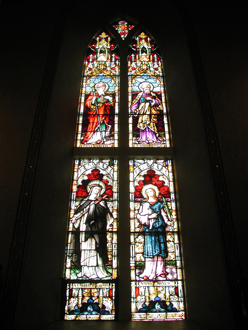 """View of Sweeney Memorial Window (1893) by ???? (????) of ???? depicting (top) """"Saint Martin"""" and """"Saint Bartholomew"""" and (bottom) """"Saint Catherine of Sienna"""" and """"Saint Agnes"""" dedicated: """"Presented By Martin And Anne Sweeney In Memory Of Martin And Mary Sweeney AD 1893""""."""