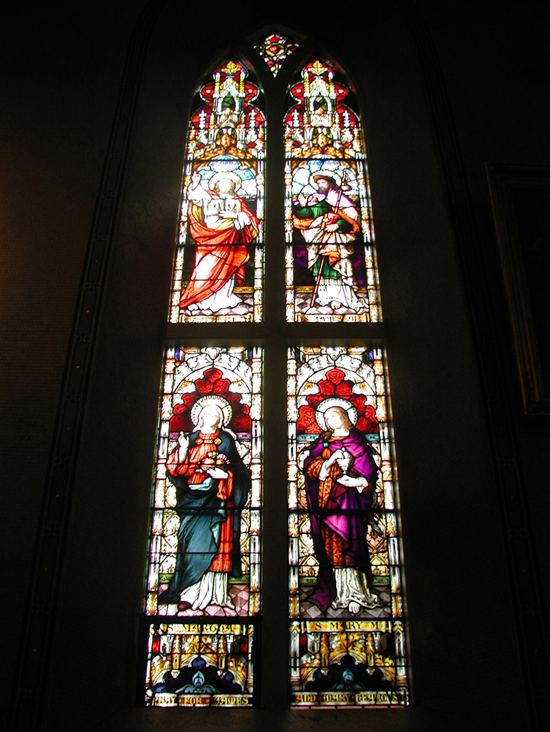 """View of Hearons Memorial Window (undated) by ???? (????) of ???? depicting (top) """"Christ our Saviour"""" and """"Saint James the Apostle"""" and (bottom) """"Saint Martha"""" and """"Saint Mary Magdalene"""" dedicated: """"Pray For James And Mary Hearons""""."""