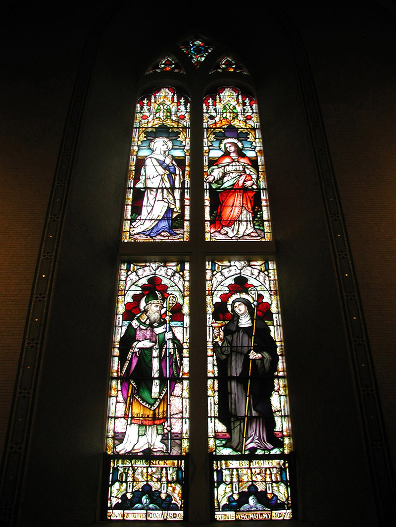 """View of Macaulay Memorial Window (1893) by ???? (????) of ???? depicting (top) """"Mater Doloros [Our Lady of Sorrows]"""" and """"Saint John"""" and (bottom) """"Saint Patrick"""" and """"Saint Bridget"""" dedicated: """"Pray For The Donors Dr. And Mrs. Macaulay AD 1893""""."""