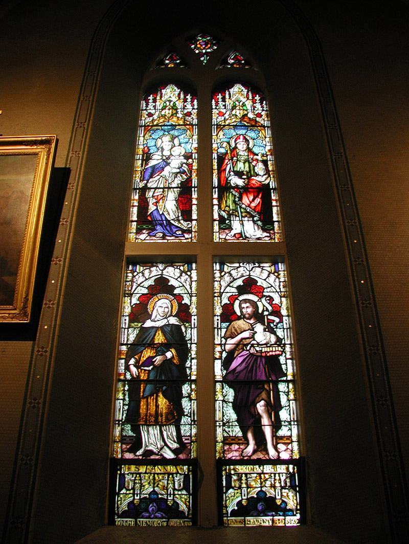 """View of Kevany Memorial Window (1893) by ???? (????) of ???? depicting (top) """"The Blessed Virgin Mary"""" and """"Saint Eugene"""" and (bottom) """"Saint Anne"""" and """"Saint John the Baptist"""" dedicated: """"To The Memory Of Owen And Agnes Kevany AD 1893""""."""